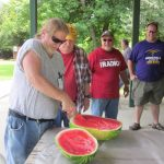 Dave, KF5CGS, cuts up the watermelon. The equipment is stowed and it's time to celebrate another successful Field Day.