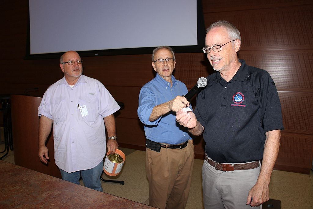 Robin Hudson and Jon Reise looking on as Frank Revitte pulls Dave Thomas', K5CGX, name as winner of the 50-50 raffle